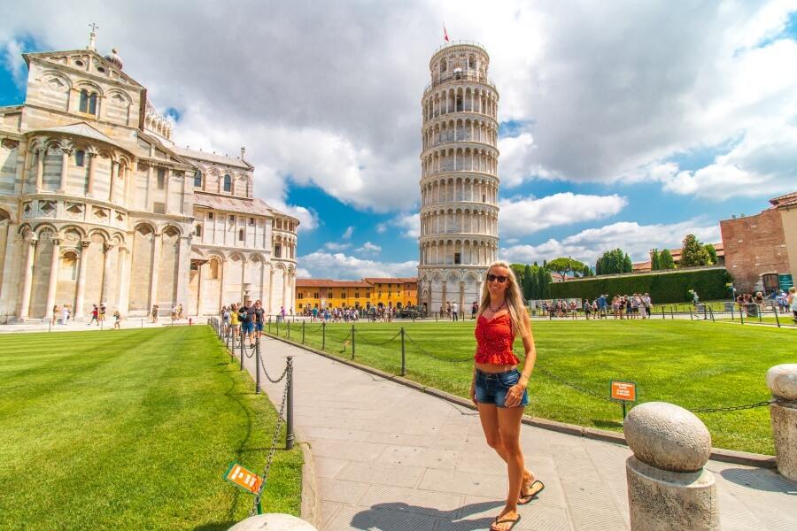 Frau steht vor schiefem Turm von Pisa