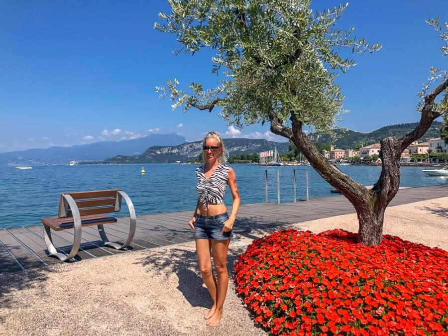 Frau steht vor rotem Blumenbeet an Seepromenade vor Sitzbank