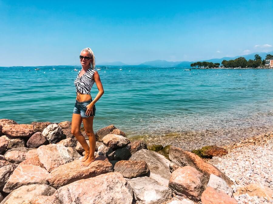 Frau steht auf Felsen am Kiesstrand am Gardasee