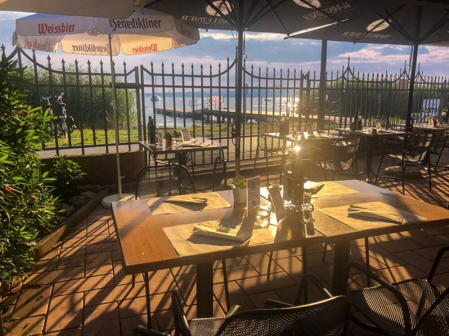 Blick auf Tisch in Restaurant mit See hinter Zaun in der Abendsonne