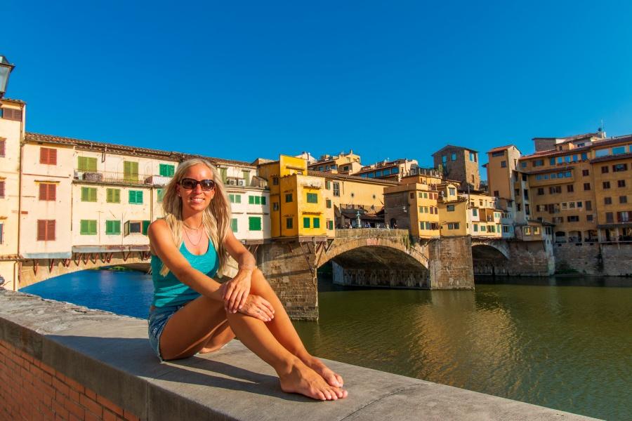 Frau sitzt auf Mauer vor ältester Brücke in Florenz