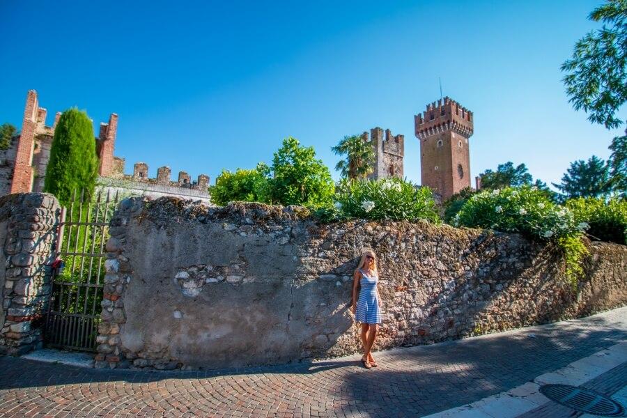 Frau im Kleid steht vor Stadtmauer in Lazise