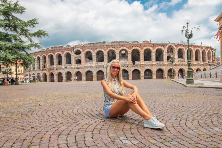 Frau sitzt am Boden vor Arena von Verona