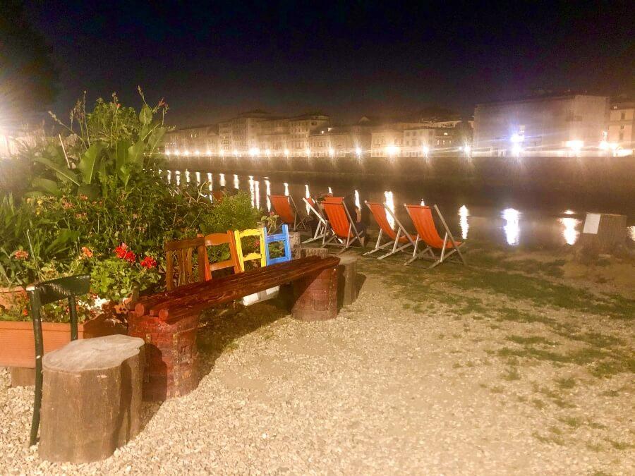 Biergarten mit bunten Stühlen direkt am Fluss Arno in Florenz