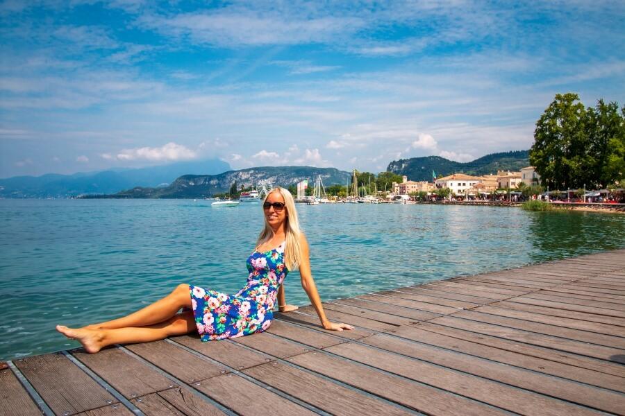 Frau sitzt an Promenade vor Gardasee auf Steg