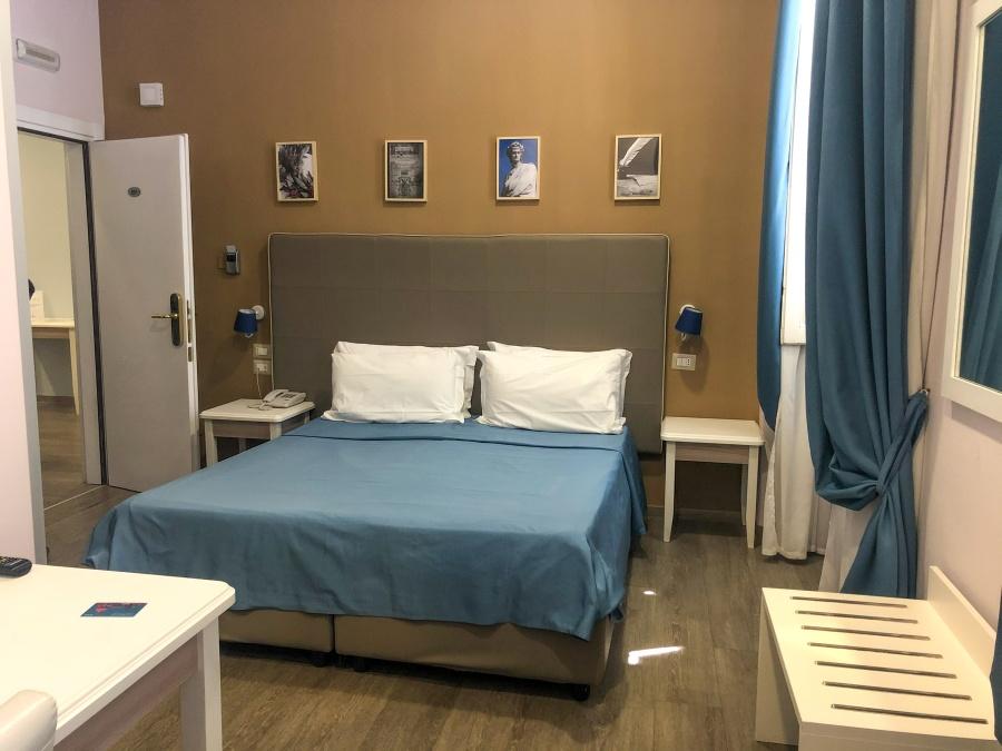 Hotelzimmer mit Doppelbett und Bildern an der Wand