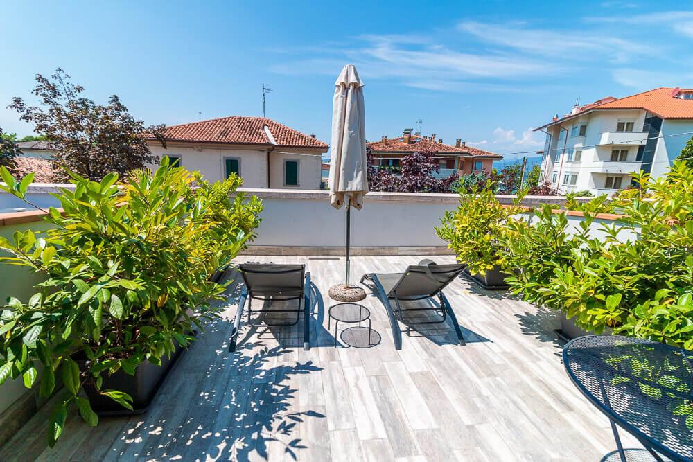 Blick auf Terrasse mit Liegen und Schirm vor Hotelzimmer