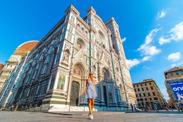 Frau im gestreiften kurzen Kleid steht vor Dom in Florenz