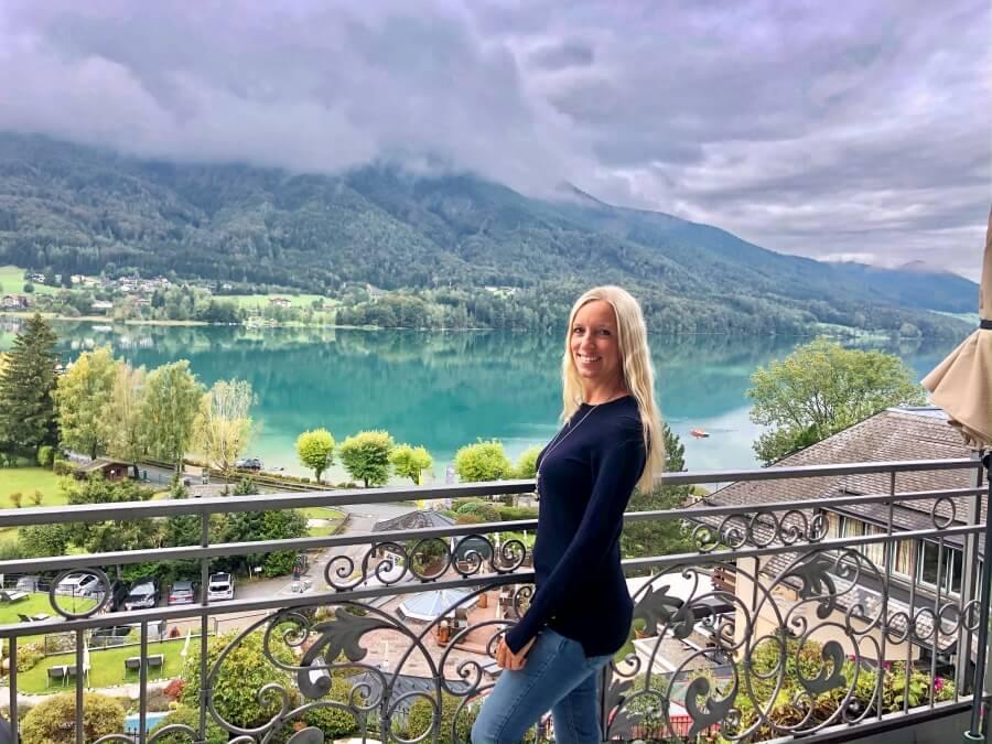 Frau steht am Balkon mit Blick auf den Fuschlsee in Österreich
