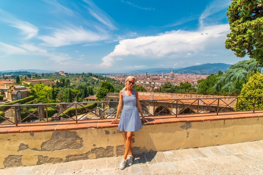 Florenz Sehenswürdigkeiten, Frau im gestreiften Kleid steht vor Mauer mit Aussicht über Florenz