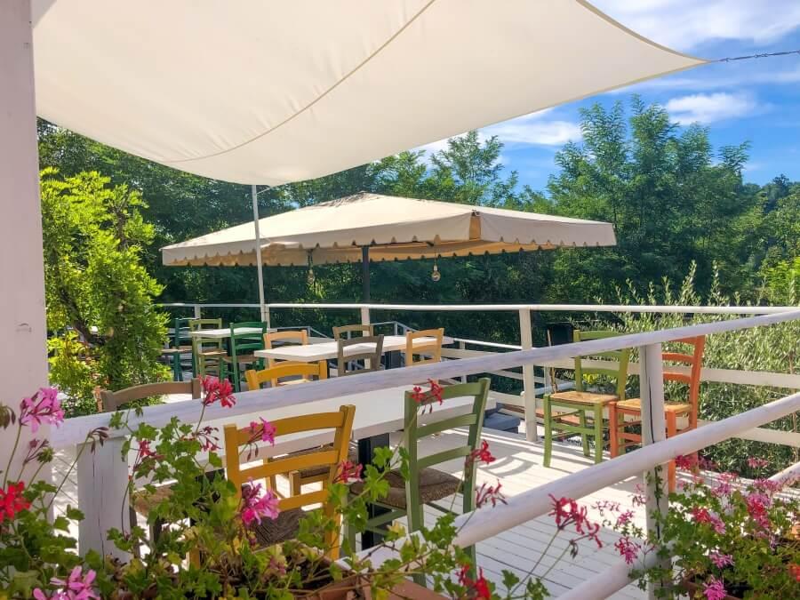 Agriturismo Villa Le Vigne, Bunte Holzstühle, weiße Tische auf Terrasse