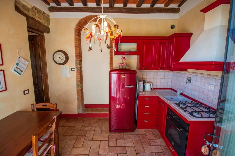 Agriturismo Villa Le Vigne, Essbereich mit roter Küche im Landhausstil