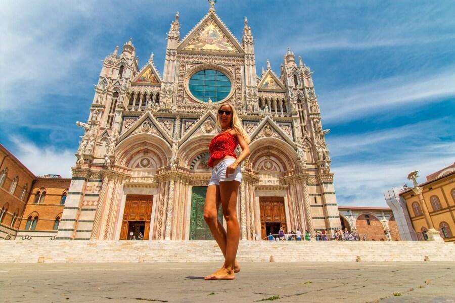 Frau steht vor Dom in Siena