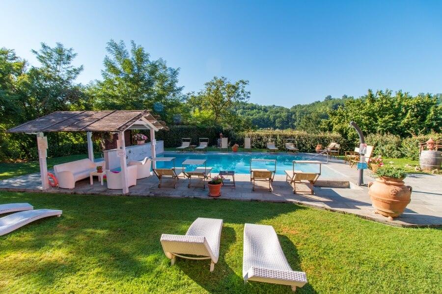 Blick auf Pool mit weißen Liegestühlen