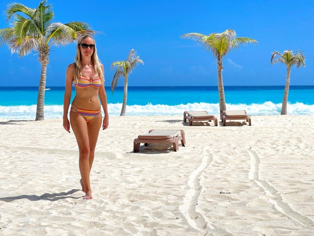 Frau am Strand mit Liegestühlen und Palmen