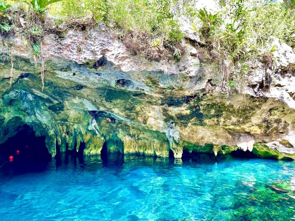 Blick auf Höhle mit kristallklarem, blauen Wasser