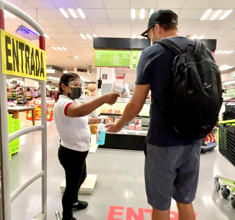 Mann im Supermarkt während Fieber gemessen und Hände desinfiziert werden